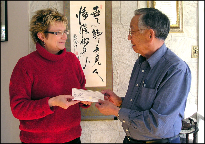Mr. Mac Nishiyama, on behalf of the  Nikkei Cultural Society of Lethbridge (Alberta) presenting Karen a cheque.